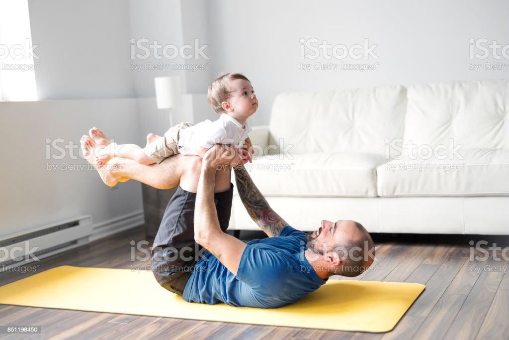 sports man is engaged in fitness and yoga with a baby at home stock photo