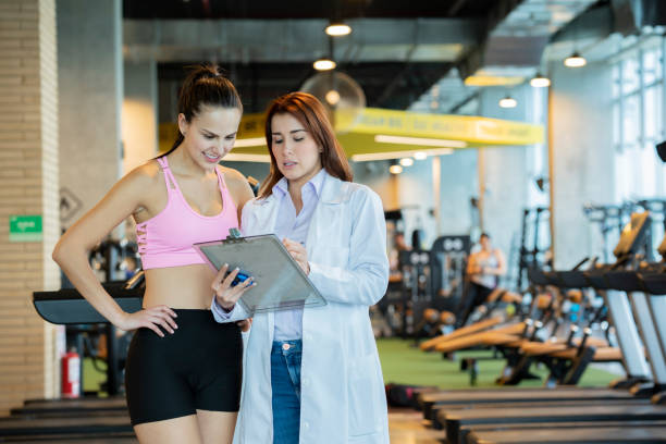 Sports medicine shows instructions to a woman athlete Sports medicine, working in a gym, is in charge of taking care of athletes, shows the instructions of a plan to follow an athlete sports medicine stock pictures, royalty-free photos & images