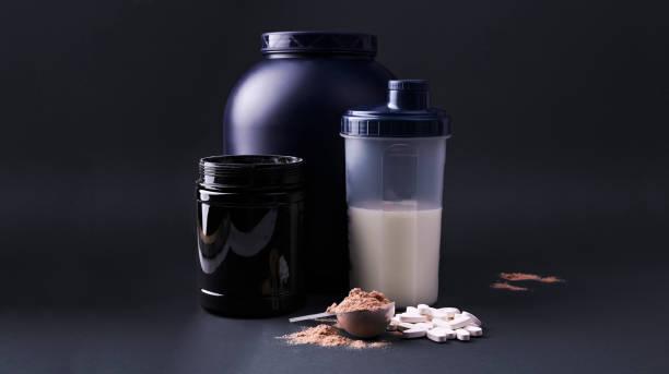 sport-nahrungsergänzungsmittel auf schwarzem hintergrund. fitness, bodybuilding, gesundes lifestyle-konzept. molkenproteinpulver in messlöffel. kopierraum - nahrungsergänzungsmittel stock-fotos und bilder