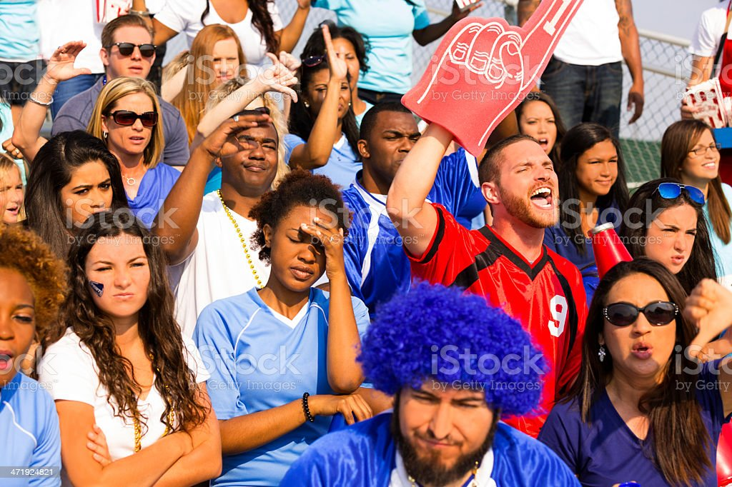 Sports: One fan cheers, others 'boo' for opposite team. stock photo