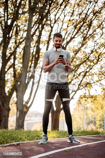 istock Sports person texting messages on the running track 1053860422