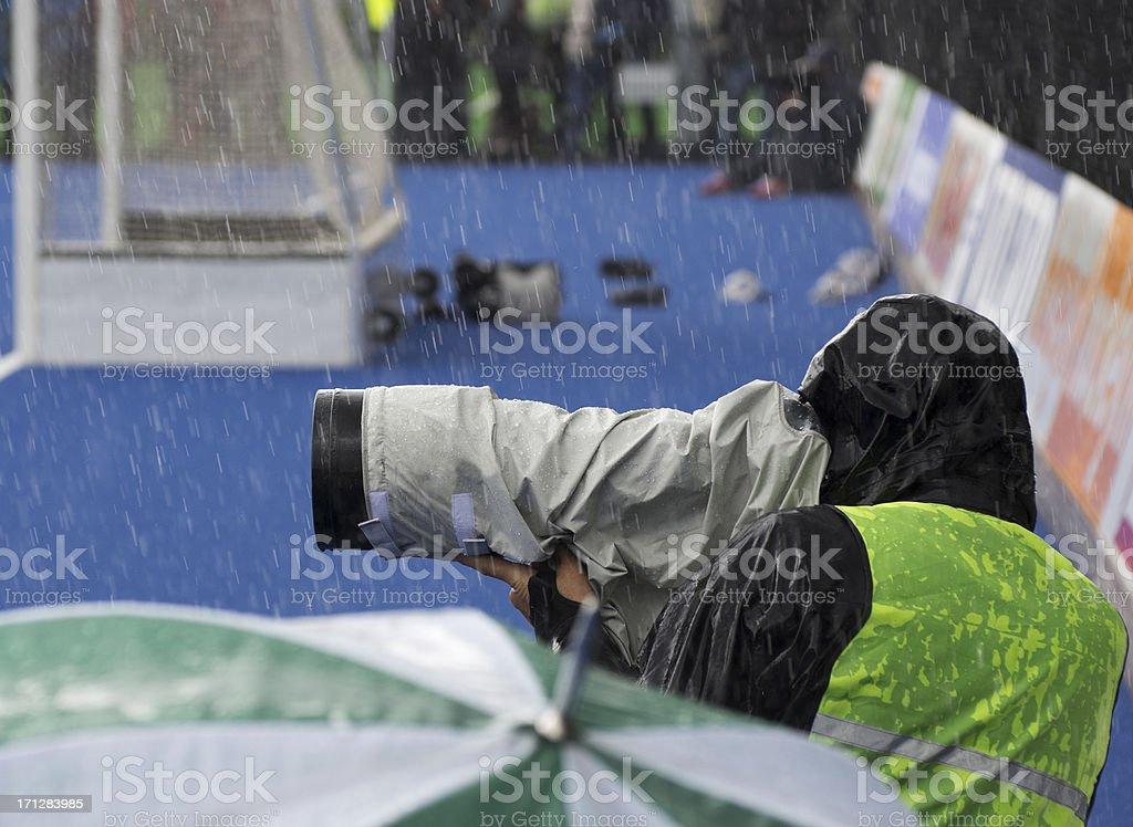 Sports photographer at work in rain stock photo