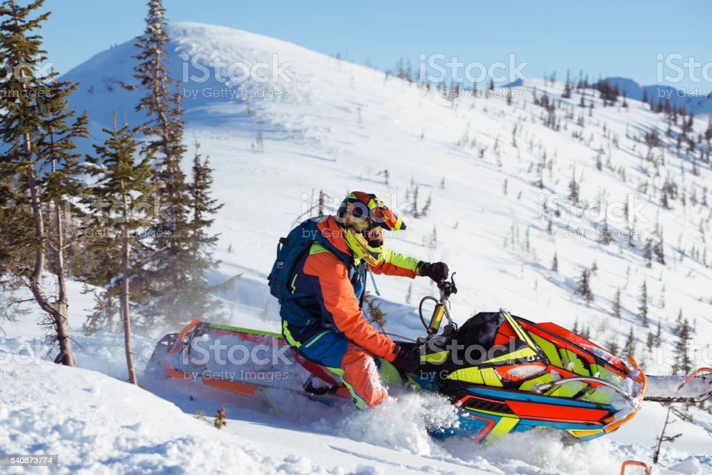 Pro driver riding on an extreme snowmobile in deep snow mountain...