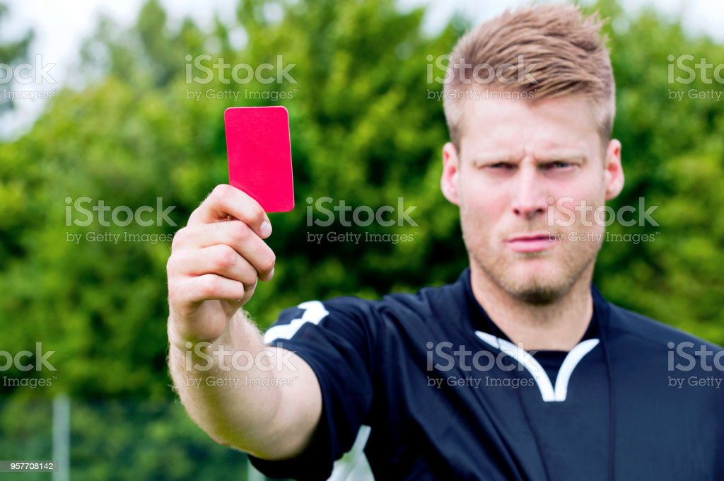 Serious referee stands on a playing field and has just blown his...