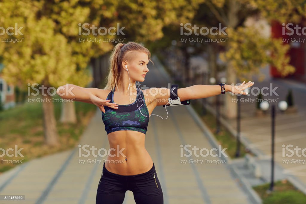 A sports runner girl makes a warm-up before jogging in a park in stock photo
