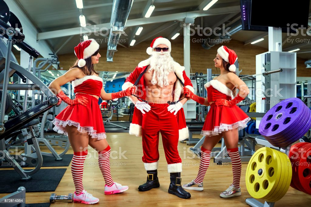 Sports Santa Claus with girls in Santa's costumes in the gym on stock photo