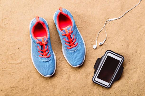 Sports shoes, earphones, smartphone against sand, studio shot. stock photo