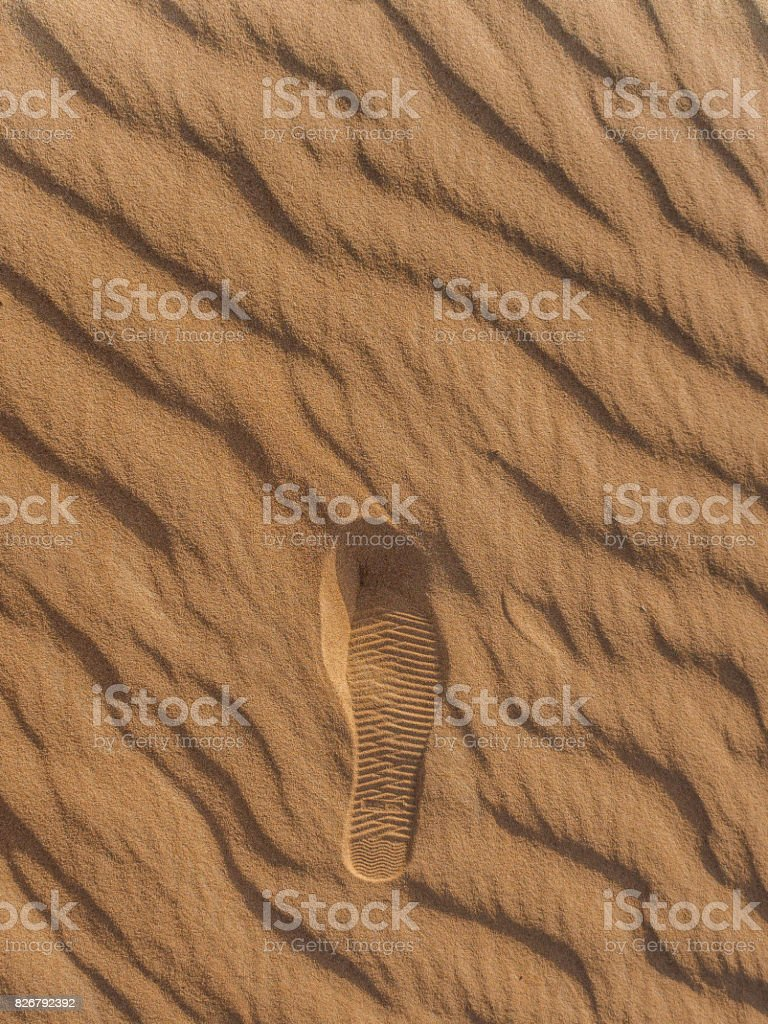 Sports shoes footprint in the sand on beach of Dubai desert stock photo