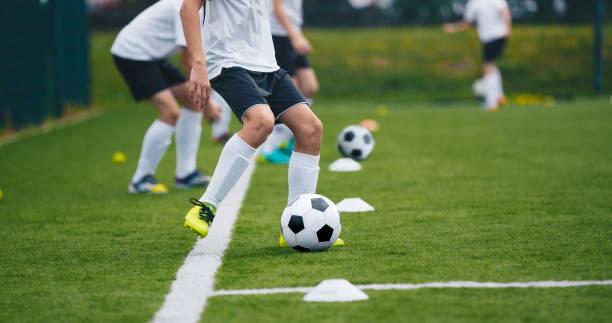 sport voetballers op training. jongens schoppen voetbalballen op oefensessie. kinderen die voetbal op het veld van het voetbal van de opleiding spelen. beginner soccer drills voor junioren - internationale voetbal stockfoto's en -beelden