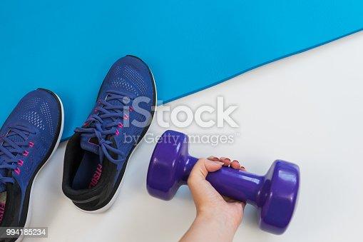 637596492istockphoto Sports, sports equipment: sneakers, dumbbells, fitness mat 994185234