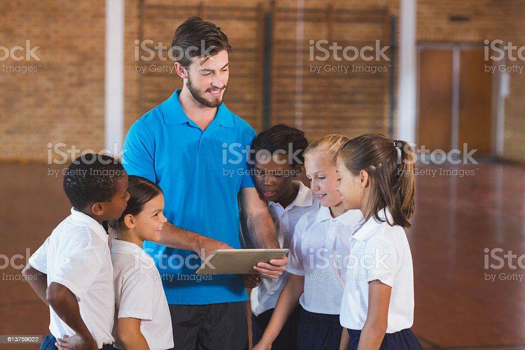 Sports teacher and kids using digital tablet in basketball court - foto de stock
