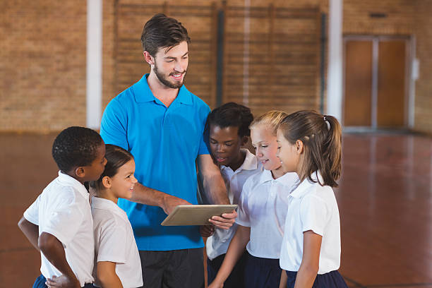 Sports teacher and kids using digital tablet in basketball court stock photo