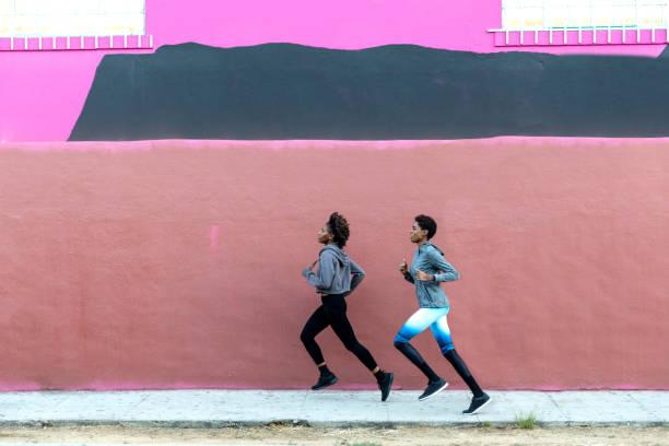 sports team running in the city. group of people getting fit - corsa su pista femminile foto e immagini stock