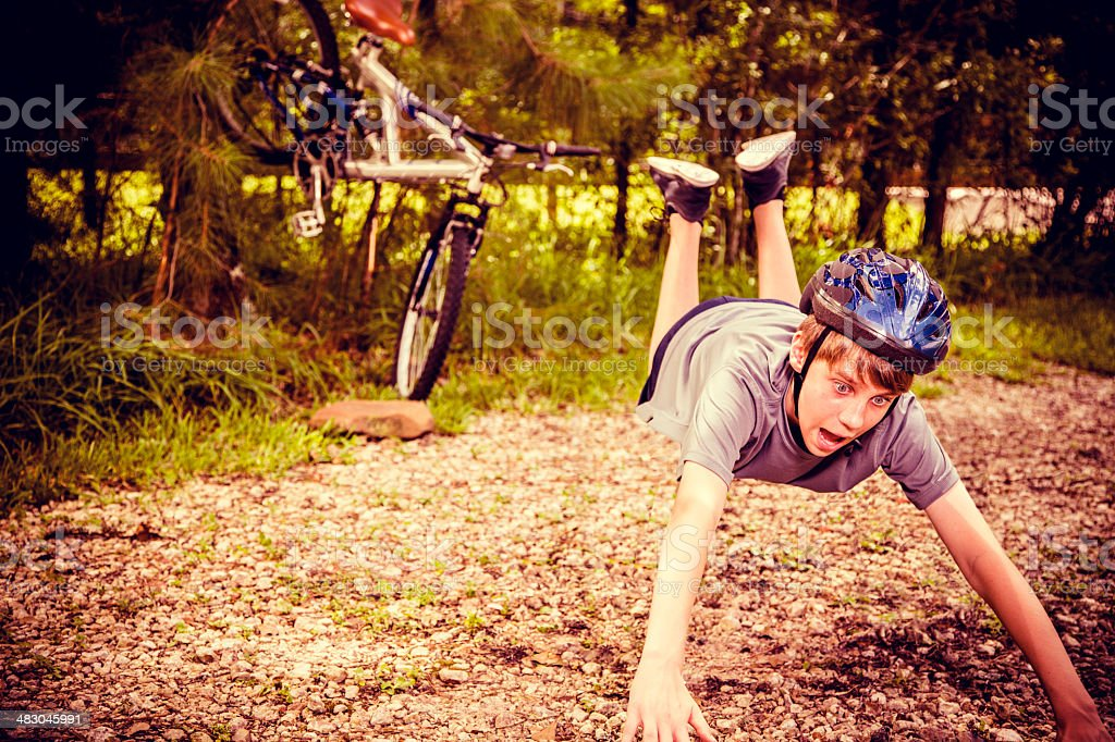 Sports: Teen boy has bicycle accident on rural road. stock photo