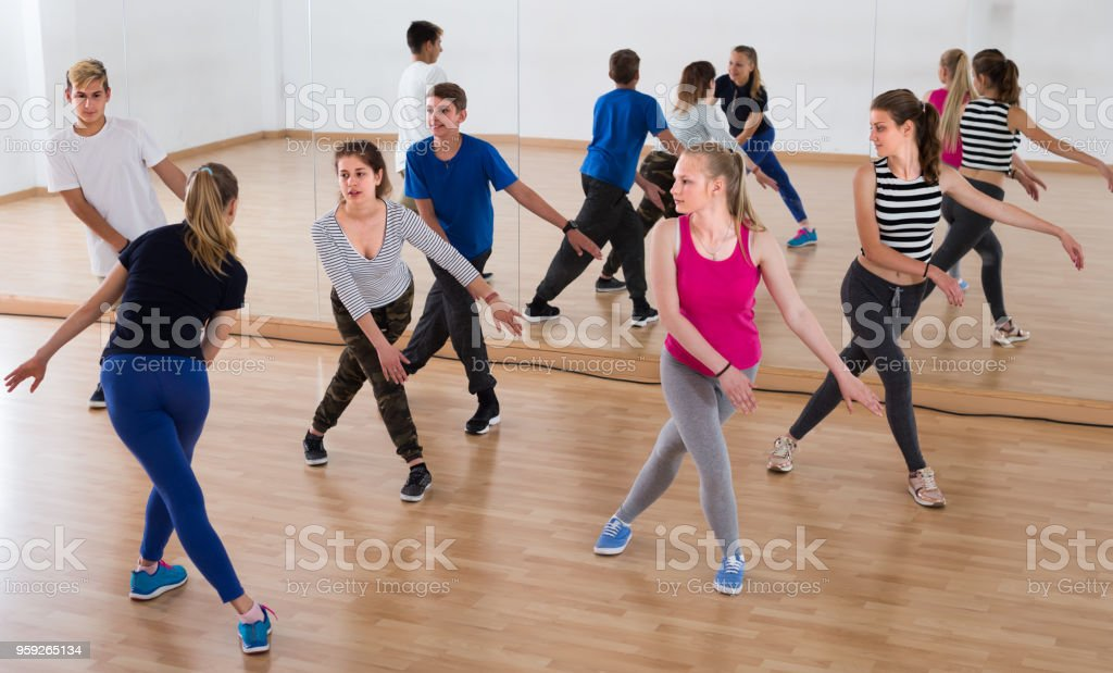 sports teenage boys and girls learning to dance in dance hall
