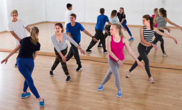 sports teenage boys and girls learning in dance hall - dance class stock photos and pictures