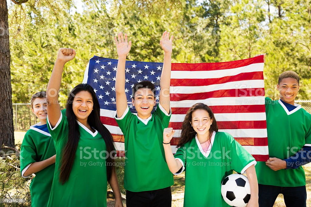 Sports: Teenage friends soccer team with USA flag background. royalty-free stock photo