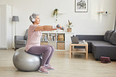 Senior woman exercising with dumbbells while sitting on fitness ball and listening to music in the room at home