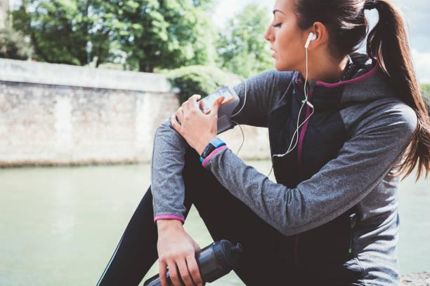 sportliche frau puls auf mobile app überprüfen - armband water stock-fotos und bilder