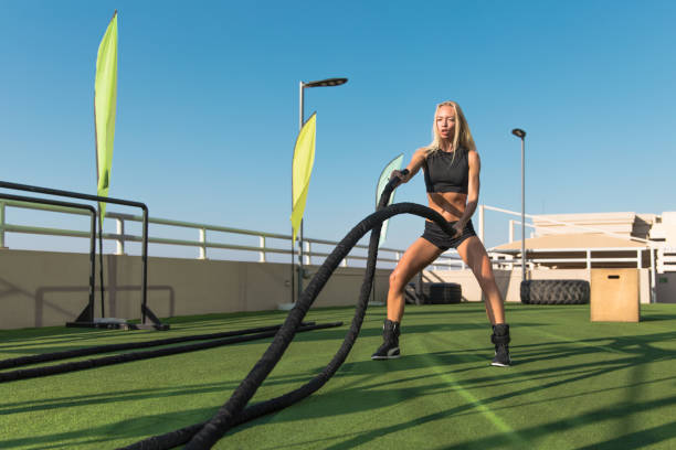 Sports woman doing battle ropes exercises in a cross training gym. stock photo