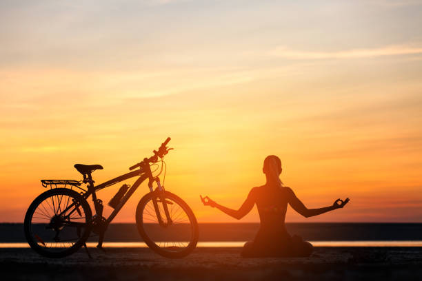 Sports woman doing yoga at sunrise on the sea beach against the background of orange sky and bicycle. Fitness concept. Lotus posture stock photo