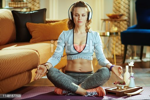 973962328istockphoto sports woman in white headphones in modern house meditating 1148157203