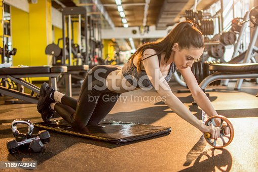 istock Sports woman is doing ab roller exercise while working out at gym 1189749942