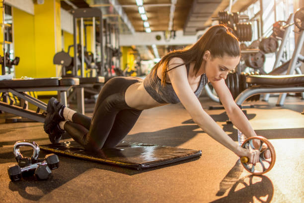 Sports woman is doing ab roller exercise while working out at gym stock photo