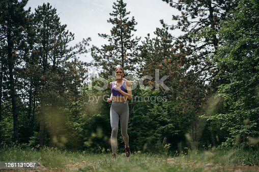 Smiling young woman jogging in the nature.