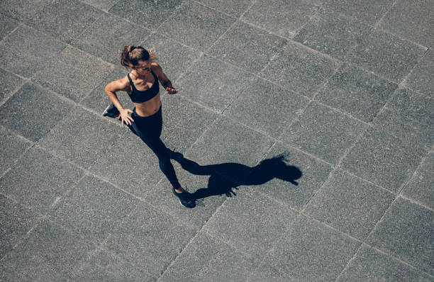 Sports woman on morning run Woman sprinting in the morning outdoors. Top view of female runner working out in the city. women's track stock pictures, royalty-free photos & images