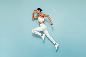 istock Sports woman running in studio. Full length shot of young female exercising over blue background. 1216658940