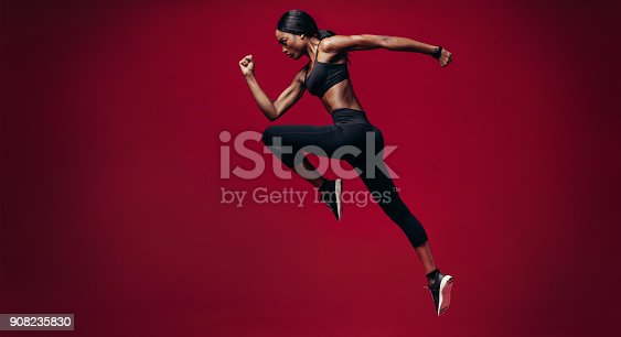 istock Sports woman running over red background 908235830