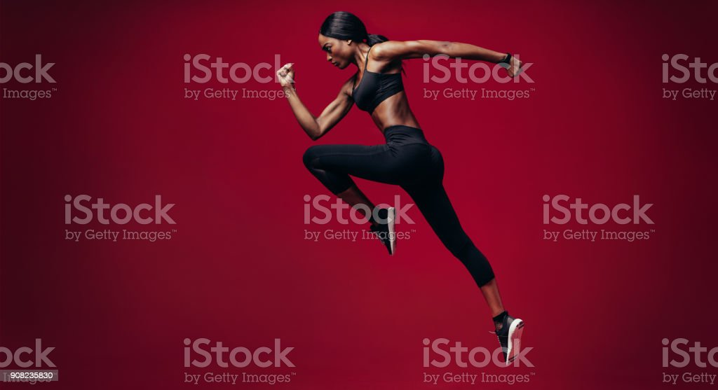 Sports woman running over red background stock photo