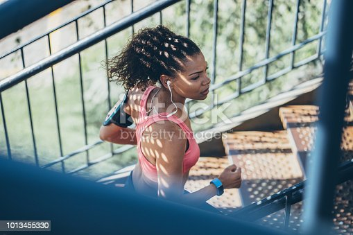 Young african-american woman running up a staircase outdoors in sunny day
