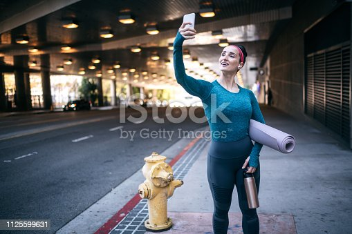 1091470492 istock photo Sports woman taking a selfie with a mobile phone on the street sidewalk 1125599631