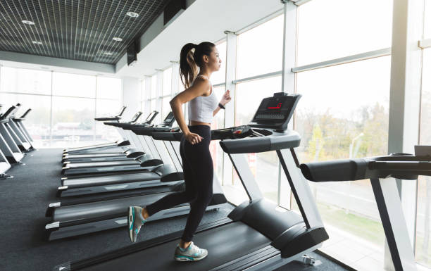 Sports woman training on treadmill near the window Sports woman training on treadmill near the window in gym treadmill stock pictures, royalty-free photos & images