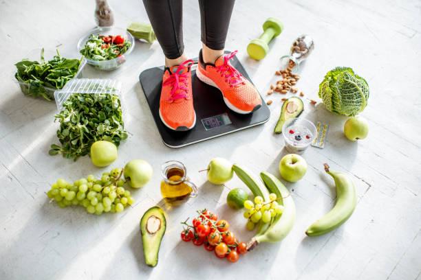 Sportvrouw met een gewicht van gezonde voeding rond foto