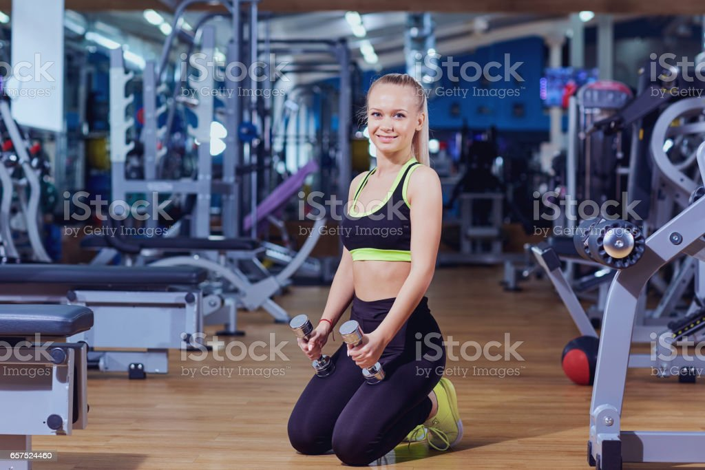 Sports woman with dumbbells in hands  the gym stock photo