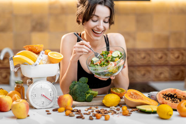 Sports woman with healthy food on the kitchen stock photo