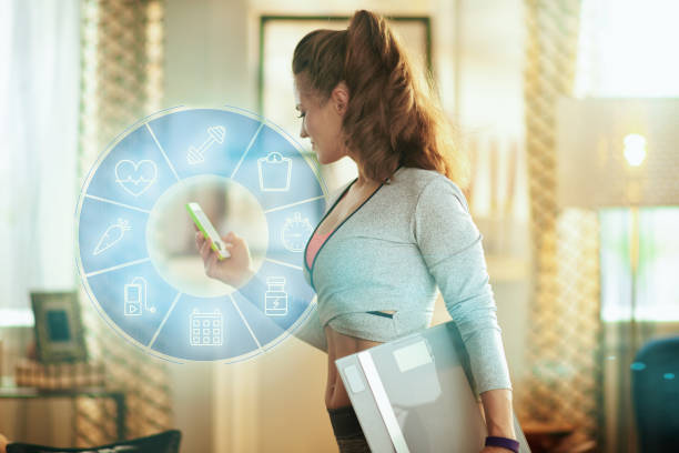 sport kvinna med smart skala spårning vikt i en fitness app - calendar workout bildbanksfoton och bilder