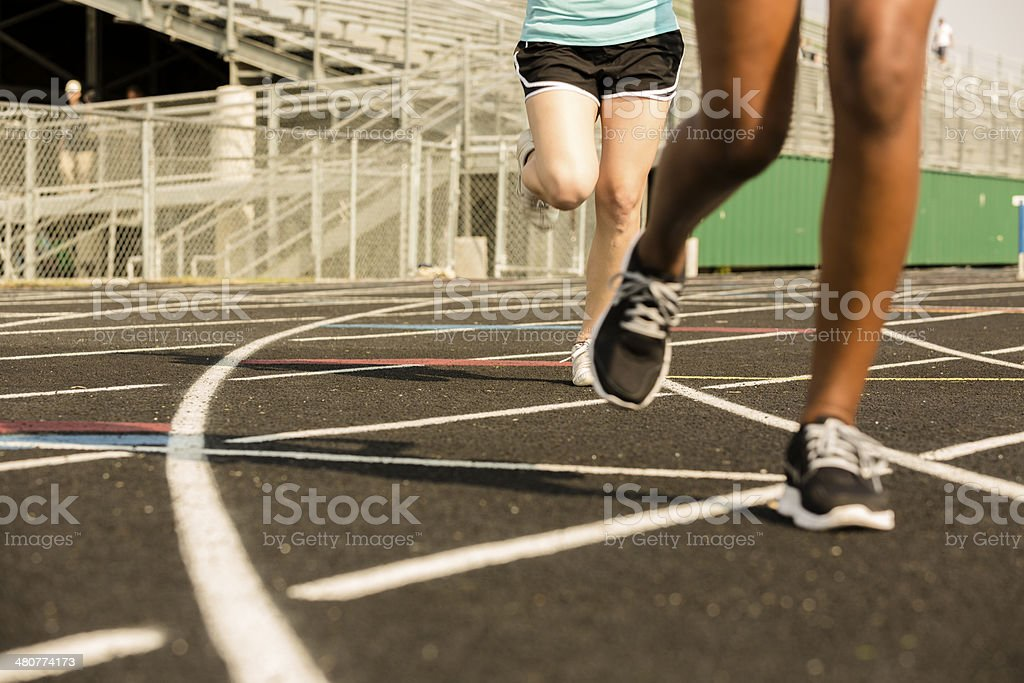 Close up of women running around a high school sports track. Stadium...
