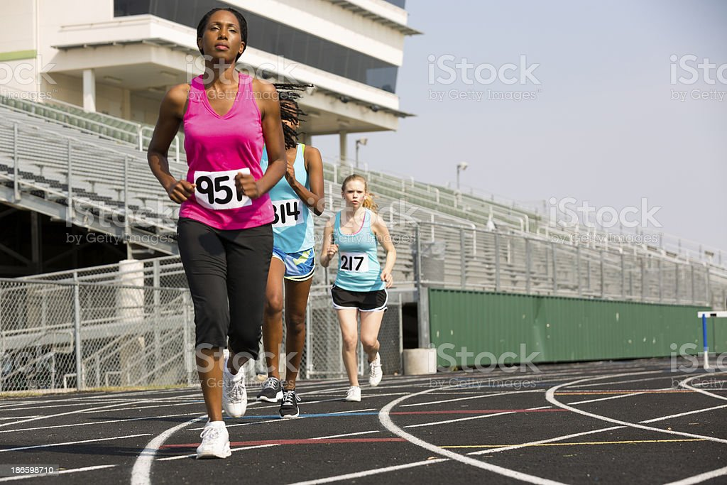 Three women run track during competitive event. Selective focus on...