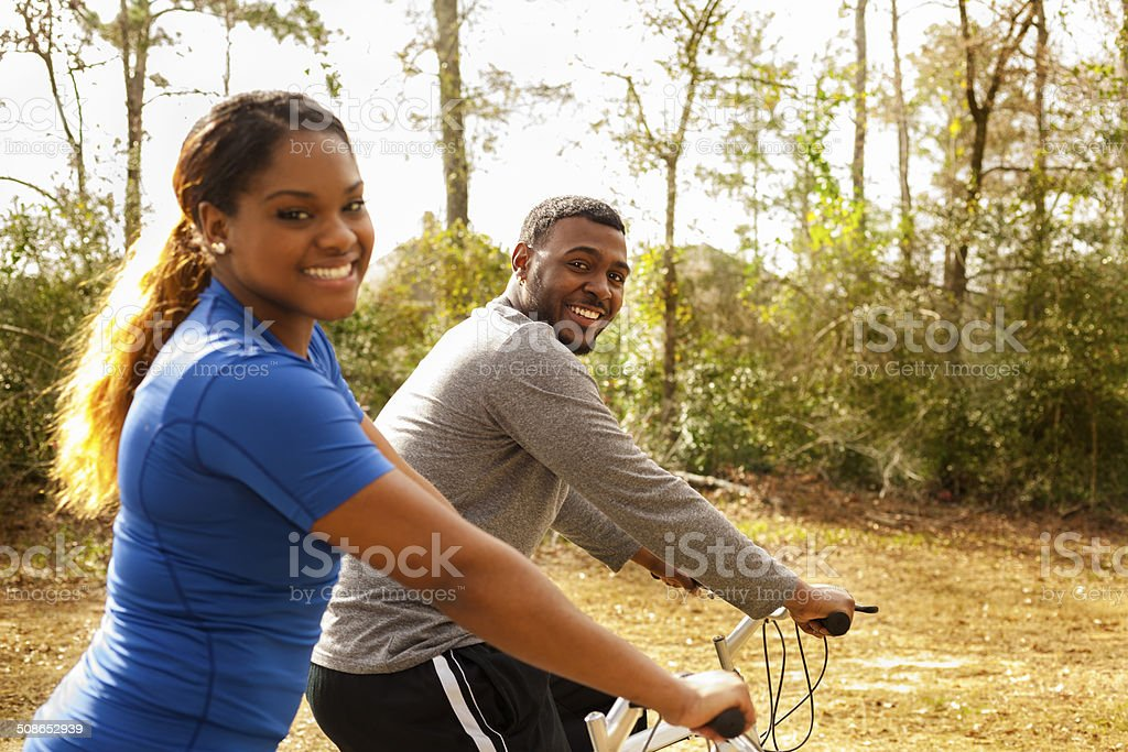 Sports: Young African descent couple ride bikes in neighborhood. stock photo