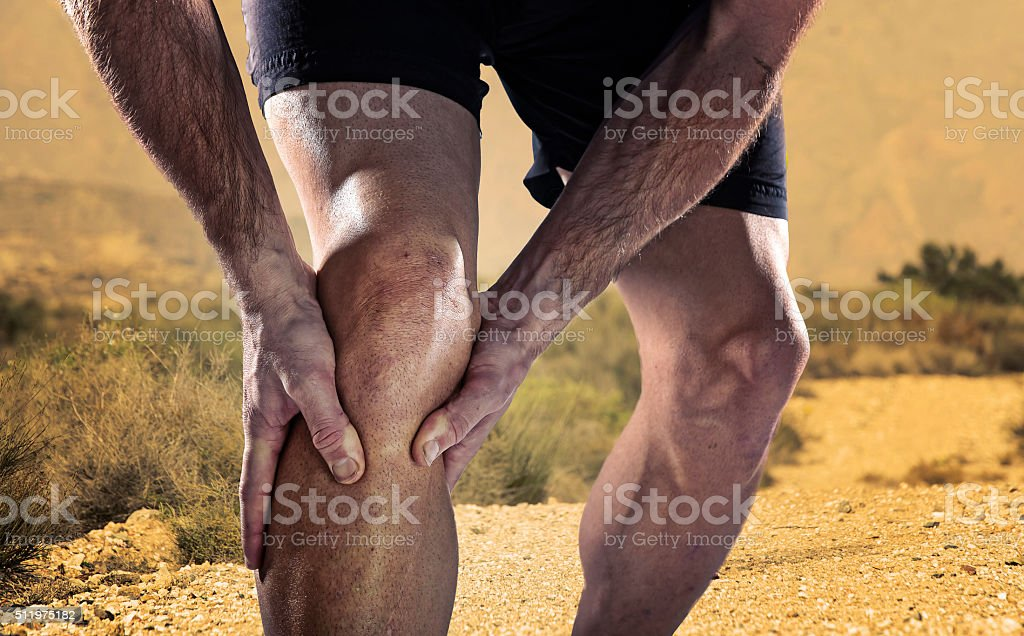 sportsman athletic legs holding knee in pain suffering muscle injury stock photo