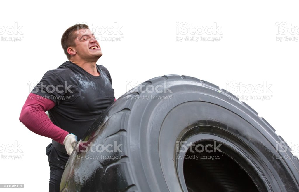 sportsman can hardly lift a car tire stock photo