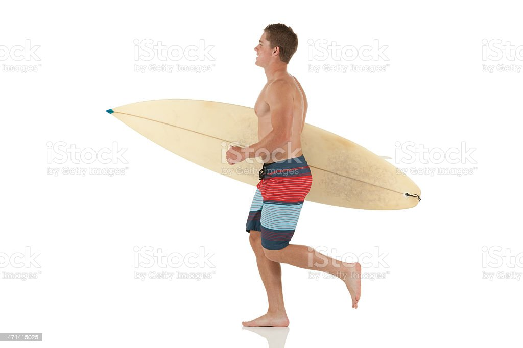 Sportsman carrying a surfboard royalty-free stock photo