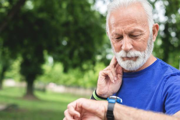 Sportsman checking watch while exercising outdoors at park stock photo