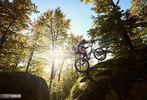 Silhouette of professional cyclist riding on back wheel on trial bicycle, sportsman making acrobatic stunt on the edge of big boulder in the forest on summer sunny day. Concept of extreme sport
