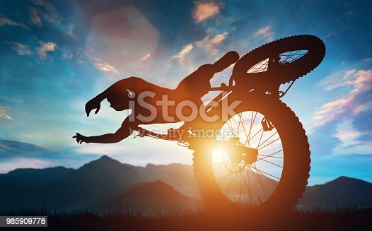istock Sportsman doing bike stunts in mountains. 985909778