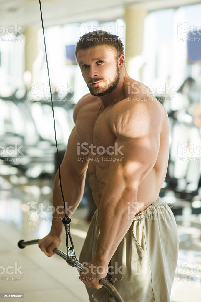 Sportsman doing pull-ups in gym. stock photo